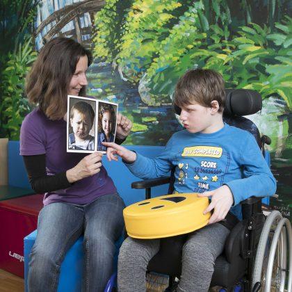 Učiteljica drži dve sliki. Na eni je deček, na drugi deklica. Fant v vozičku kaže s prstom na sliko deklice.