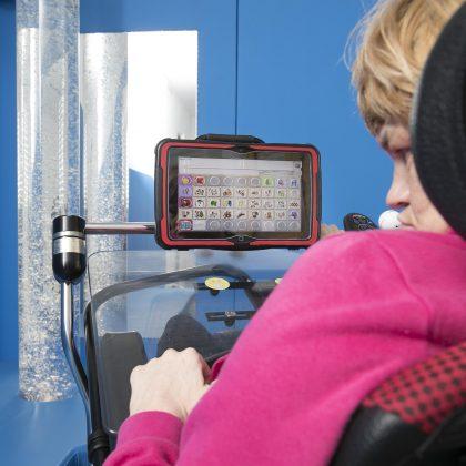 Uporabnica na vozičku igra igrico na tablici.