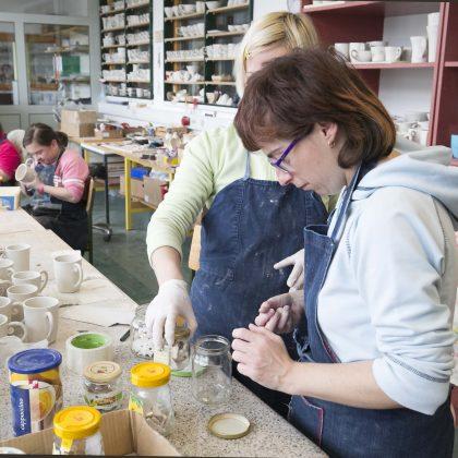 Več oseb izdeluje keramične skodelice.