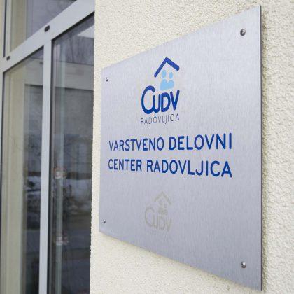 Plošča ob vratih z napisom Varstveno Delovni Center Radovljica.