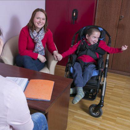 Otrok se smeji v invalidskem vozičku.