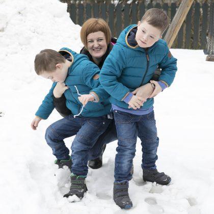 Na snegu se ženska igra z dvema otrokoma.