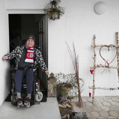 Gospod na vozičku oblečen v zimska oblačila gre nasmejan skozi vrata.
