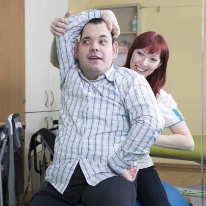 Uporabniku zaposlena pomaga dvigniti roko čez glavo pri vaji.
