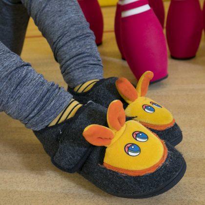 Nekdo ima obute copate z motivom rumenega zajčka.