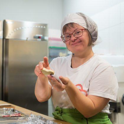 Uporabnica v predpasniku znamke Biseri v kuhinji drži v roki Sandrin srček.