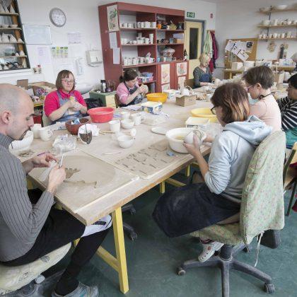 Skupina obdeluje keramiko.